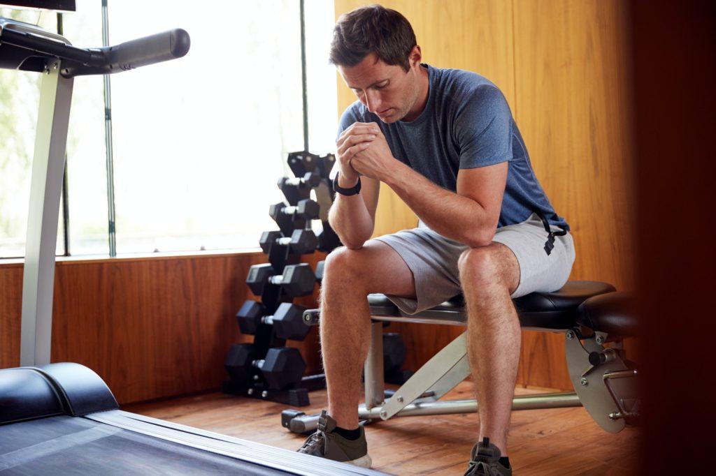homme anxieux assis sur une machine de salle de sport