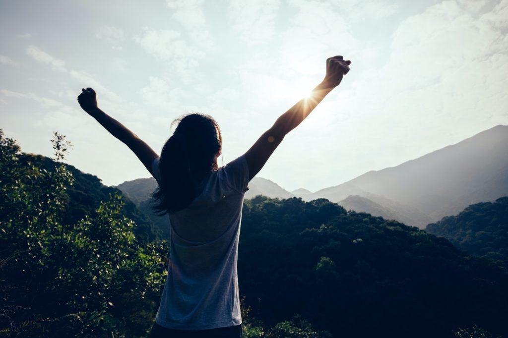 femme lève les bras devant un beau paysage