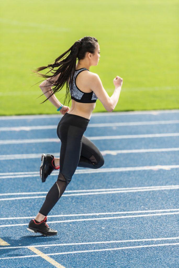 woman athlete running on tracks