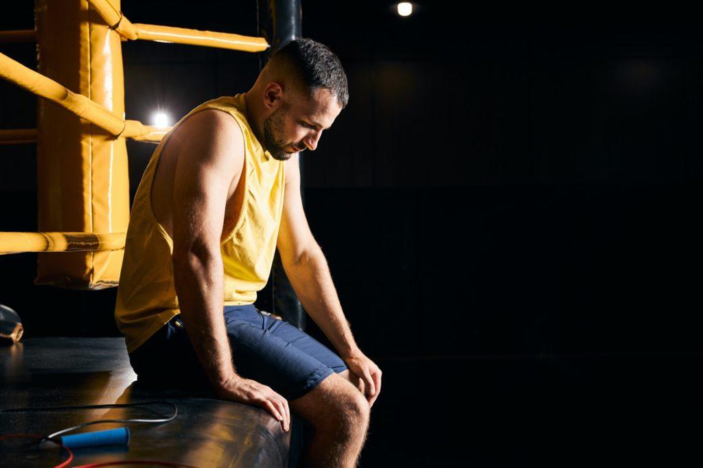 boxeur assis sur le bord du ring l'air triste