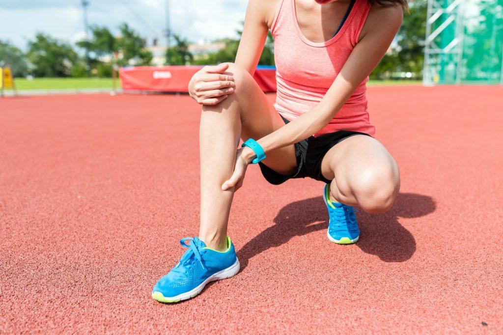 coureuse se tient la jambe après une blessure